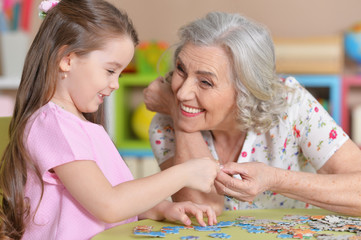 Cute little granddaughter and grandmother collecting puzzles