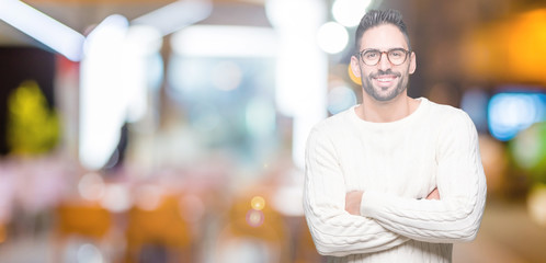 Young handsome man wearing glasses over isolated background happy face smiling with crossed arms looking at the camera. Positive person.