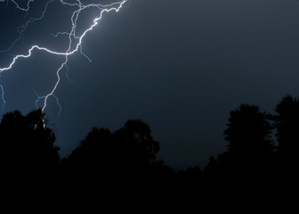 lightsning striking over trees during a night storm