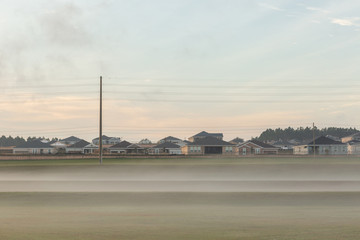 Small town covered in fog at sunrise