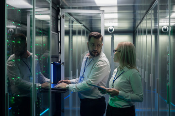 Adult man and woman using tablet and laptop while diagnosing server hardware in modern data center