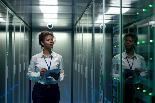 African American woman using tablet while walking in corridor of data center and checking hardware on server racks