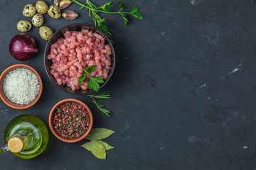 Homemade minced meat in a black bowl over dark slate