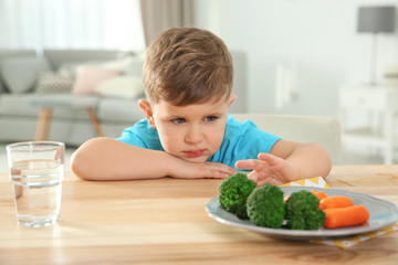 Unhappy little boy refusing to eat vegetables at table in room