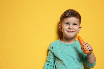 Adorable little boy with carrot on color background. Space for text
