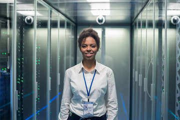 Adult IT worker in white shirt standing among server racks in data center smiling at camera