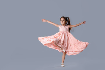 little girl in pink dress posing on gray background.