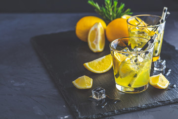 Lemon alcohol drink cocktail with ice, lemon and rosemary