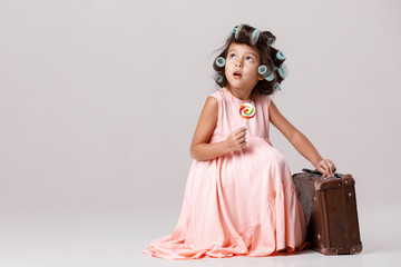 f79e3d88d Funny little girl in pink dress and hair curlers holding lollipop ...