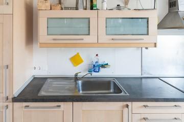 Einbauküche in einer Wohnung mit Elektrogeräten und Arbeitsplatte und Schubladen und Hängeschrank