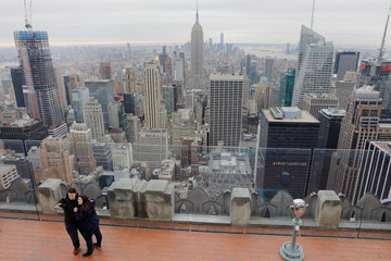Tourists take photographs from the Top of the Rock observation desk as the Empire State Building rises above New York in the background