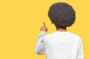 Young african american man with afro hair wearing sporty sweatshirt Posing backwards pointing behind with finger hand