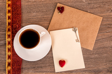 Cup of coffee with cookies, red ribbon, key, card on wooden background