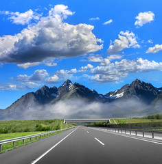Road to the mountain. Automobile highway on the background of the picturesque rocky mountains.