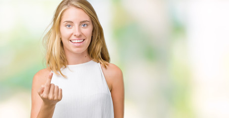 Beautiful young elegant woman over isolated background Beckoning come here gesture with hand inviting happy and smiling