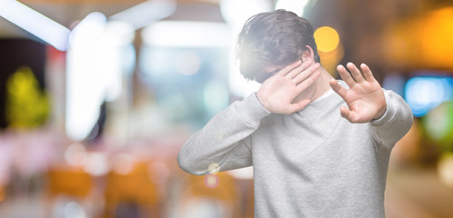 Young handsome sporty man wearing sweatshirt over isolated background covering eyes with hands and doing stop gesture with sad and fear expression. Embarrassed and negative concept.