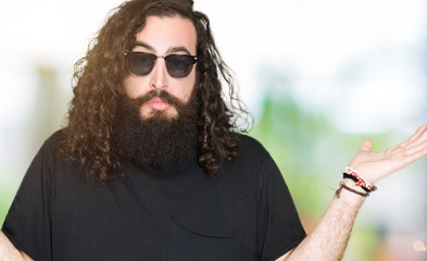 Young hipster man with long hair and beard wearing sunglasses clueless and confused expression with arms and hands raised. Doubt concept.