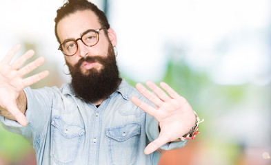 Young hipster man with long hair and beard wearing glasses Smiling doing frame using hands palms and fingers, camera perspective