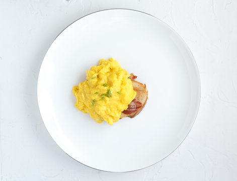 Scrambled eggs on plate over white stone background. Top view, flat lay