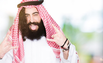 Arabian business man with long hair wearing traditional keffiyeh scarf shouting with crazy expression doing rock symbol with hands up. Music star. Heavy concept.