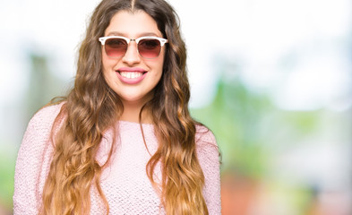 Young beautiful woman wearing sunglasses and pink sweater with a happy and cool smile on face. Lucky person.