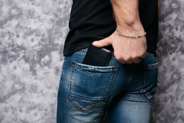 social networks in the pocket of street jeans: a man with an elastic ass pulls out a smartphone from the back pocket of his pants. men's ass close-up. the guy uses a mobile phone for communication and