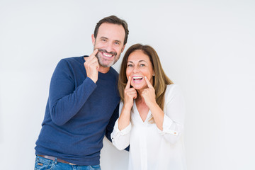 Beautiful middle age couple in love over isolated background Smiling with open mouth, fingers pointing and forcing cheerful smile
