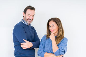 Beautiful middle age couple in love over isolated background looking confident at the camera with smile with crossed arms and hand raised on chin. Thinking positive.