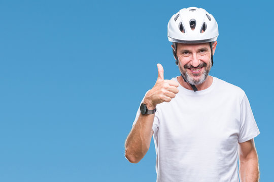 Middle age senior hoary cyclist man wearing bike safety helment isolated background doing happy thumbs up gesture with hand. Approving expression looking at the camera with showing success.