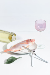 Fresh raw fish on a plate. Table setting. Creative concept.