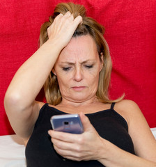 Desperate woman looking at her smartphone lying on the bed in a tank top