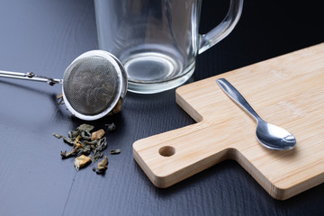 Brewing tea on a black table. Mug with a warm drink.