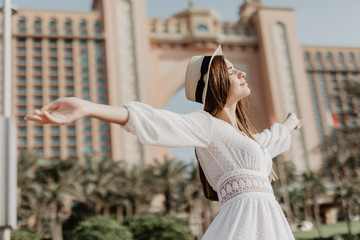 Young beauty woman in straw hat with raised hands walking outdoors in the city street
