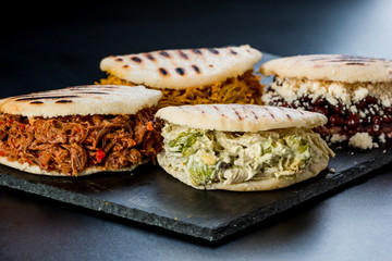 Venezuelan Latin American food, 4 arepas of different stuffing on a black table. Arepa with mechada meat, queen pepeada, black beans with white cheese and chicken