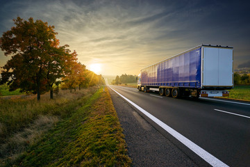 Fotobehang - Blue truck driving on the asphalt road towards sunset around line of trees in misty autumnal landscape