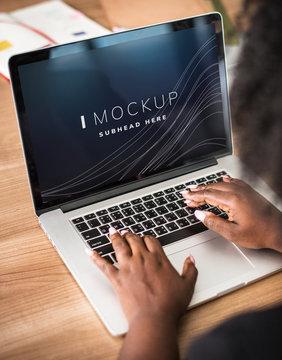 Woman working on a laptop screen mockup