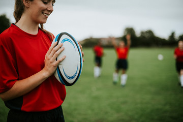 Happy female rugby player holding a ball