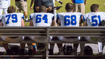 High School football players get coached from the bench