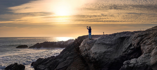 Tourist doing mobile photography with a cell phone standing on the rocks along the Malibu beach coastline in California during sunset.