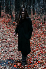 Brutal depressive Gothic stylish long haired man in autumn forest