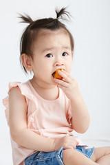Asian little girl eating fruit, in white background