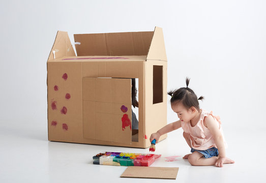 Asian little girl playing with paper house, in white background