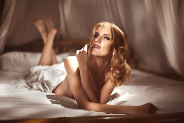 Sensual young woman lying naked or nude in canopy bed in the morning