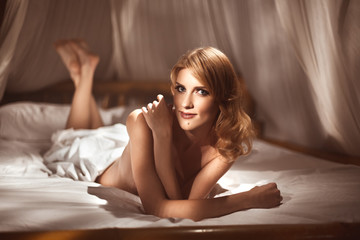 Attractive young woman lying naked or nude in canopy bed in the morning
