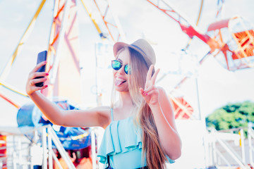 Adorable young girl smiling, showing her tongue and doing selfie with the mobile device at an amusement park. She wears sunglasses and a hat. Portrait of lifestyle