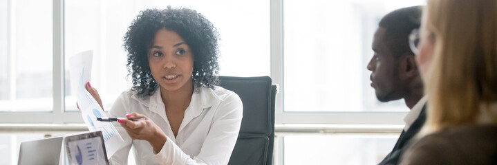 Horizontal photo multiracial people led by african businesswoman, leader showing paper financial report to clients partners negotiating at meeting sitting a boardroom, banner for website header design