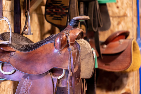 Closeup view of a saddle on a rack in a tack room.