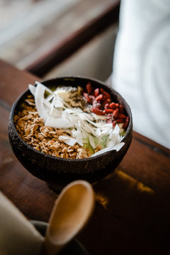 Green smoothie bowl with goji, coconut chips and granola topping on light wooden table. Food photography, healthy eating  concept. Copy space