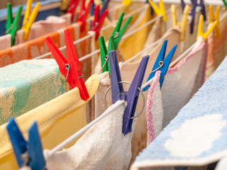 Close up of plastic clothespin on a clotheshorse with drying linen.