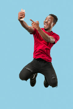 always on mobile. Full length of handsome african young man taking phone while jumping against blue studio background. Mobile, motion, movement, business concepts